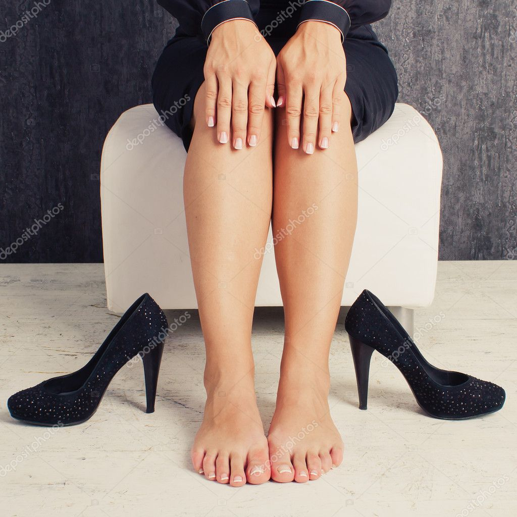 Legs of business woman sitting in black suit with shoes - Stock Image