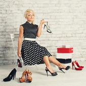 Shopaholic blond meisje in jurk zittend met schoenen en vakken — Stockfoto