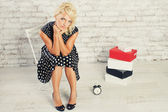 Young blonde girl in dress sitting with clock in studio — Stock Photo