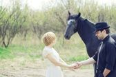 Just wedded young couple with horse dressed retro — Stock Photo