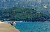 Yacht en amarrage avec les montagnes en arrière-plan — Photo