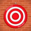 Red target on brick wall — Stock Vector