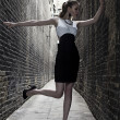 German blonde tall fashion model in a London Passing Alley posing wearing black white dress — Stock Photo