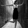 German blonde tall fashion model in a London Passing Alley posing wearing black white dress — Stock Photo #11990552