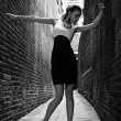 German blonde tall fashion model in a London Passing Alley posing wearing black white dress - Stock Photo