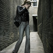 German blonde tall fashion model in a London Passing Alley posing wearing urban outfits - Stock Photo