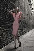 Modelo de moda alta rubia alemana en un callejón paso londres posando vestido blanco rosa — Foto de Stock