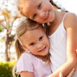 Two sisters near a tree — Stock Photo #10771759