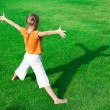 Stock Photo: A girl standing on the grass looking at his shadow