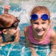 Two little girls playing in the pool — Stock Photo