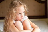 Sad child sits on the bed — Stock Photo