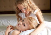 Two sad girls on the bed — Stock Photo