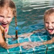 Two little girls playing in the pool — Stock Photo #11172733
