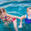Two little girls playing in the pool — Stock Photo #11172882