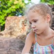 Sad little girl on the background of an old brick wall - Stok fotoğraf