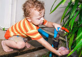 Child pouring water from the tap — Stockfoto