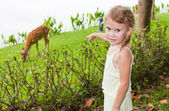 The girl in the park shows on deer — Stock Photo