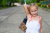 Child goes on the road with a bag in his hands — Stock Photo