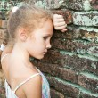 Sad little girl on the background of an old brick wall — Stock Photo #11190375