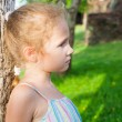 Sad little girl near a tree - Stock Photo