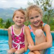 Two little girls playing in the pool — Stock Photo #11193735