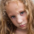 Sad little girl on the background of an old wall — Stock Photo #11342220