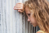Sad little girl on the background of an old wall — Stock Photo