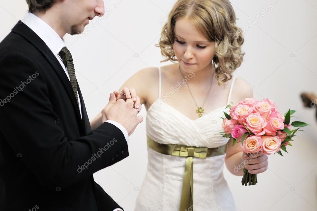 Bride putting a wedding ring on groom's finger, focus on rings — Photo #10997801