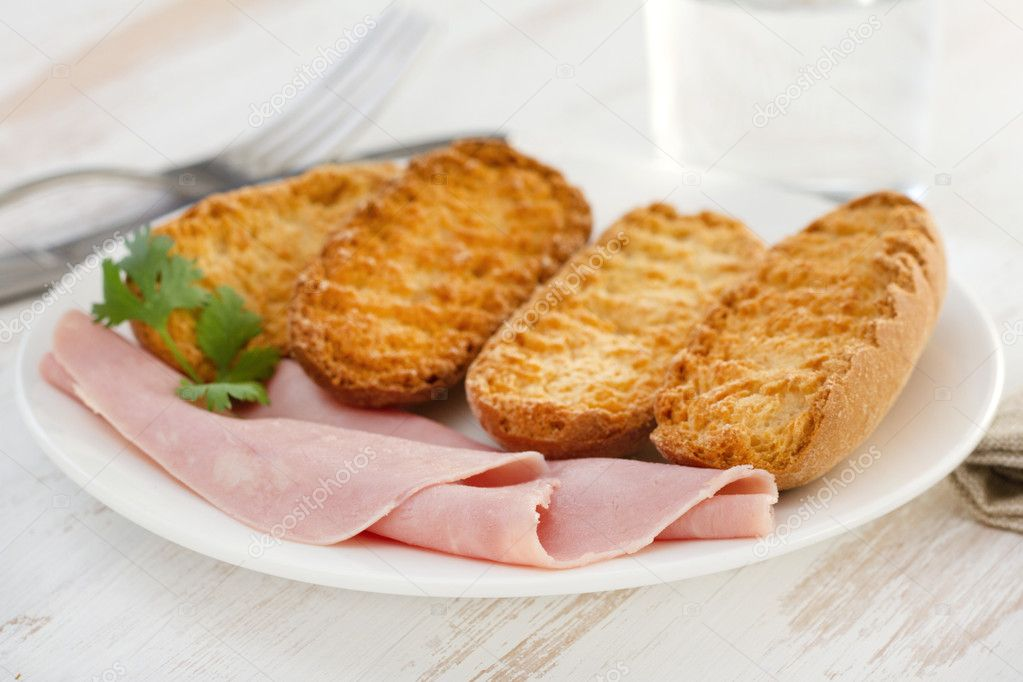 Toasts with ham on the white plate — Stock Photo #12173916