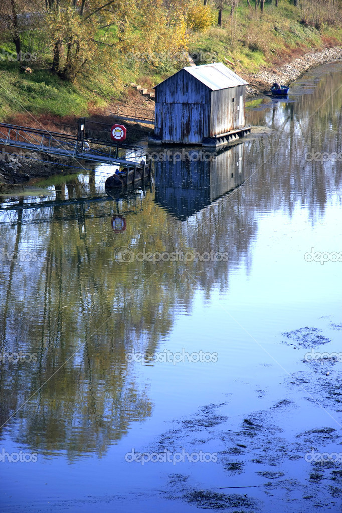 Old wooden house in the river with reflection  Stock Photo #11979177