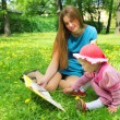 Girl and mother reading the book in spring park — Stock Photo