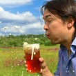 Young man blowing away beer foam, nature background — Stock Photo