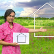 Stock Photo: Young mholding white board with house on green meadow