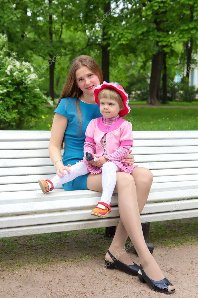 A young mother sitting on a park bench with her daughter in her arms  Stock Photo #11093098