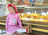Little girl sitting in the shop — Stock Photo