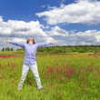 Young man standing on a meadow on a blue sky background — Stock Photo