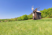 Old wind mill on a spring meadow with blue sky — Stock fotografie