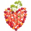 Strawberries and cherries with greens in heart shape — Stock Photo