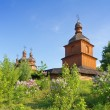 Old wooden church and lilac trees - Stock Photo