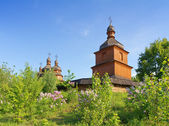 Old wooden church and lilac trees — Stock Photo