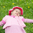 Little girl in hat lying on the lawn — Stock Photo