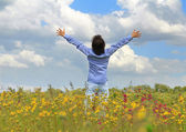 Man standing on a meadow with raised hands — Stock Photo