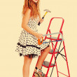 Pretty pin up woman on a ladder with a hammer and saw, toned in — Stock Photo