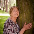 Happy senior woman in forest - Stock Photo