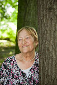 Happy senior woman in forest — Stock Photo