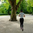Young beautiful caucasian woman jogging in summer park. - Stock Photo