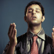 Praying Indian young businessman - Stock Photo