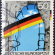 图库照片: GERMANY - CIRC1990: stamp printed in Germany dedicated to first anniversary of fall of Berlin Wall, circ1990