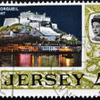 JERSEY - CIRCA 1990: A stamp printed in Jersey shows Mont Orgueil by night, circa 1990 - Stock Photo