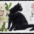 UNITED KINGDOM - CIRCA 1995: A stamp printed in England, shows the Black cat and Lilium, circa 1995 — Photo